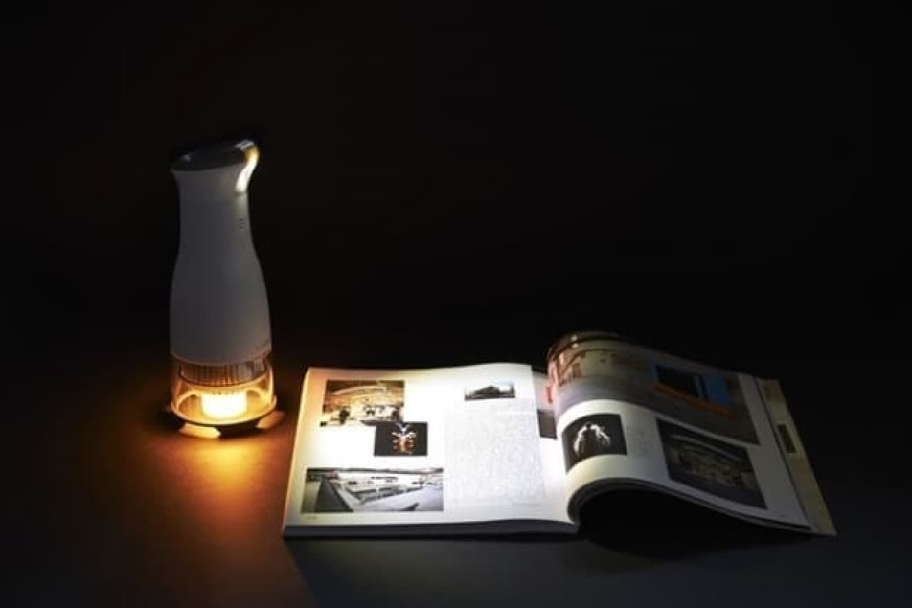 「Lumir C」の明るさを示す例:  キャンドルの熱で発電してLEDを発光させると、本が読める光量を得られる
