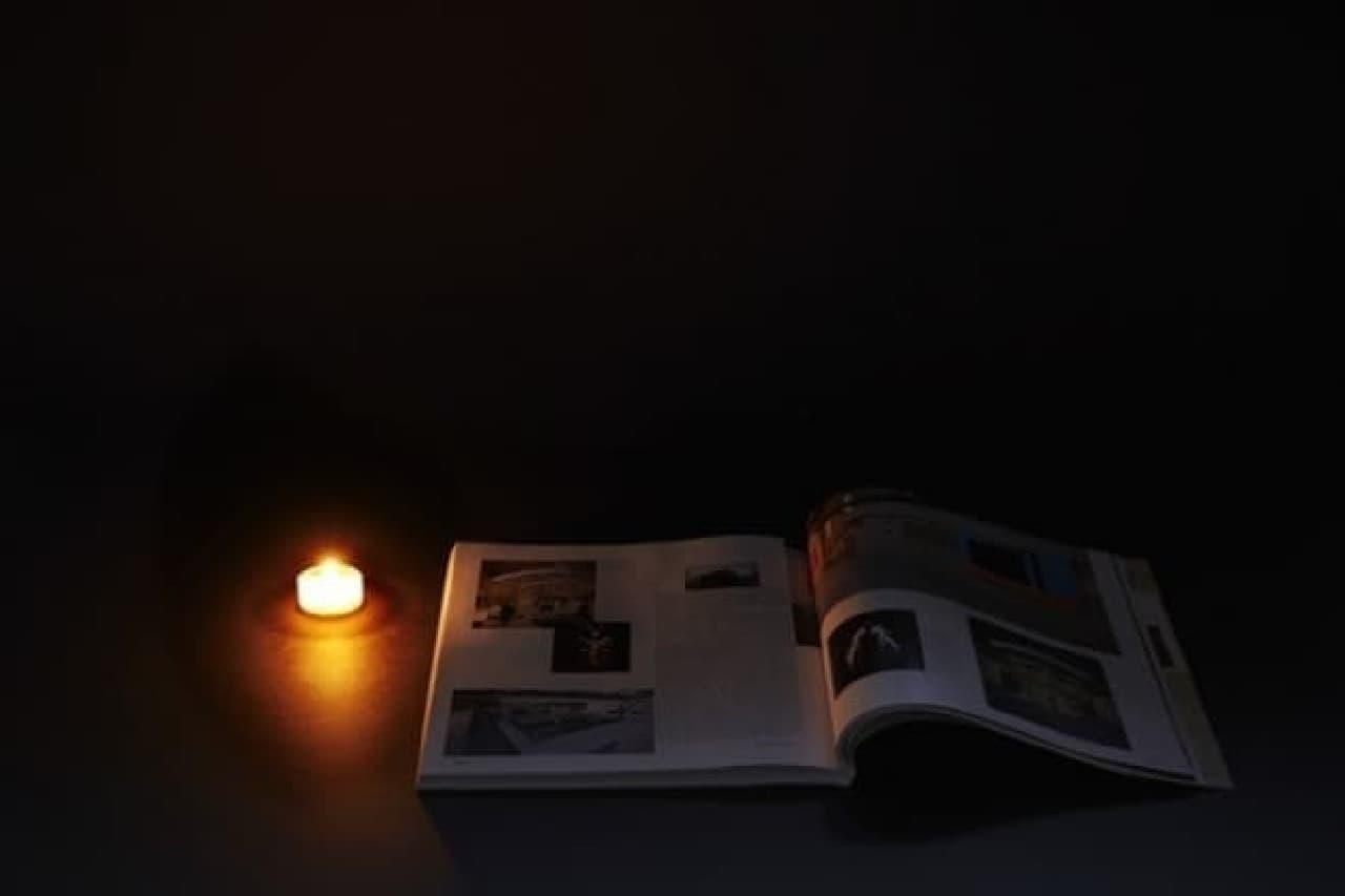 「Lumir C」の明るさを示す例:  キャンドル単体では、光量が不足し、本を読むのは困難