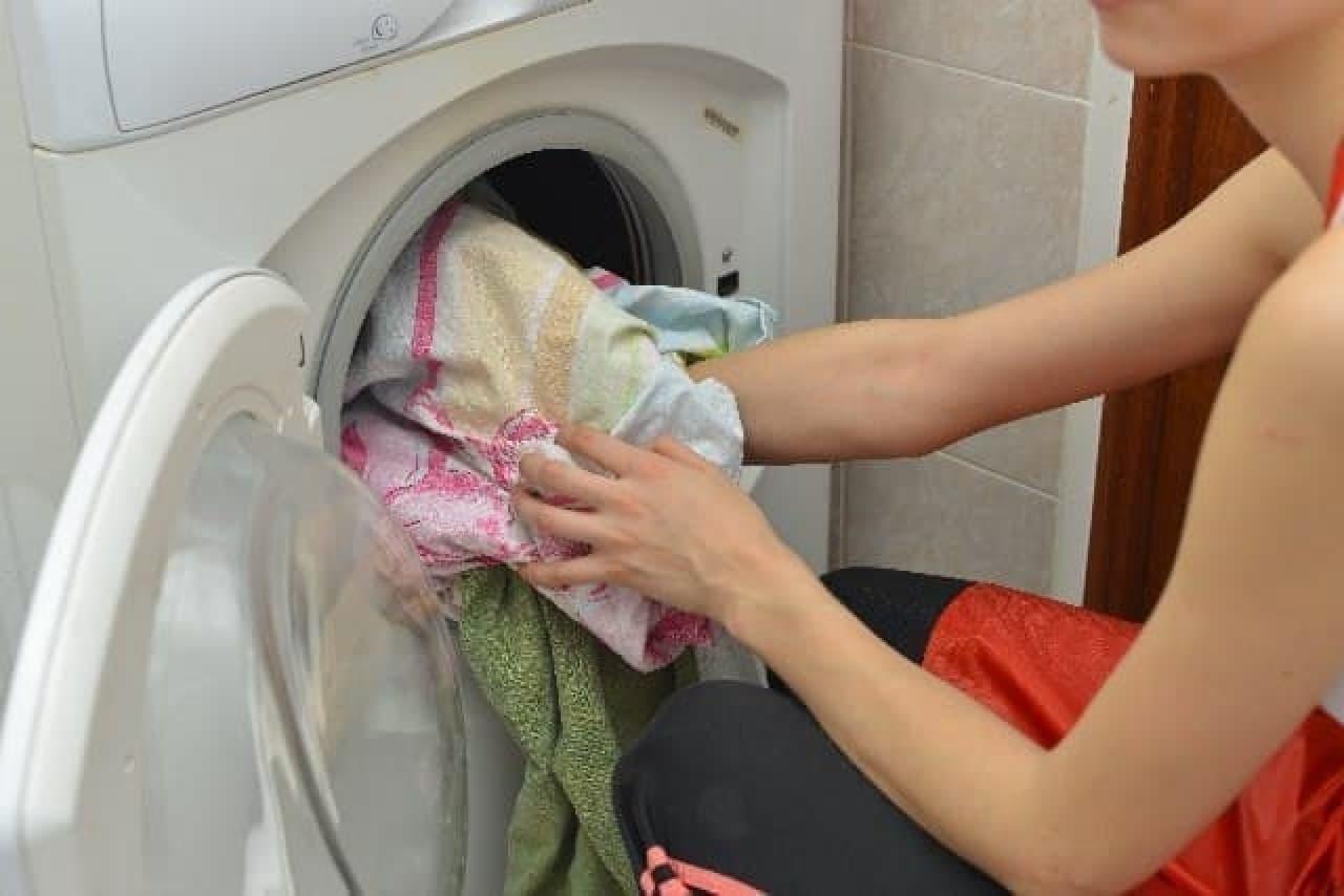 洗濯機に衣類を入れる人